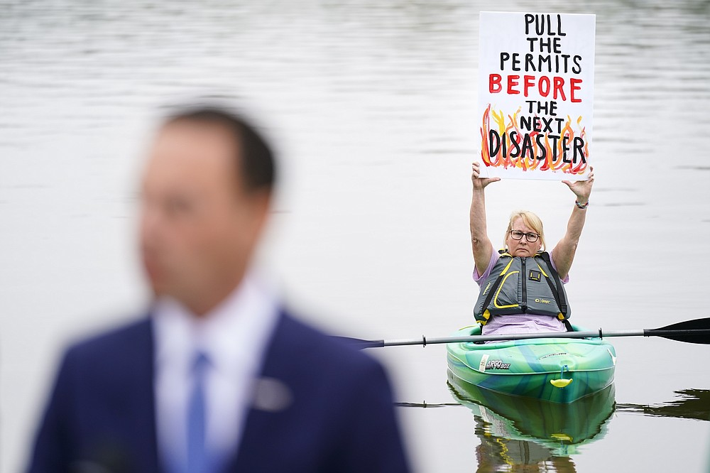 Libby Madarasz displays a placard as Pennsylvania Attorney General Josh Shapiro speaks during a news conference at Marsh Creek State Park in Downingtown, Pa., Tuesday, Oct. 5, 2021. Shapiro filed criminal charges Tuesday against the developer of a problem-plagued pipeline that takes natural gas liquids from the Marcellus Shale gas field to an export terminal near Philadelphia. (AP Photo/Matt Rourke)