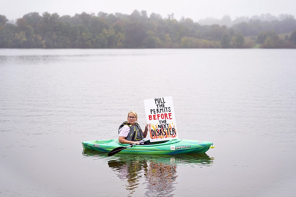 Libby Madarasz displays a placard before Pennsylvania Attorney General Josh Shapiro's news conference at Marsh Creek State Park in Downingtown, Pa., Tuesday, Oct. 5, 2021. Shapiro filed criminal charges Tuesday against the developer of a problem-plagued pipeline that takes natural gas liquids from the Marcellus Shale gas field to an export terminal near Philadelphia. (AP Photo/Matt Rourke)