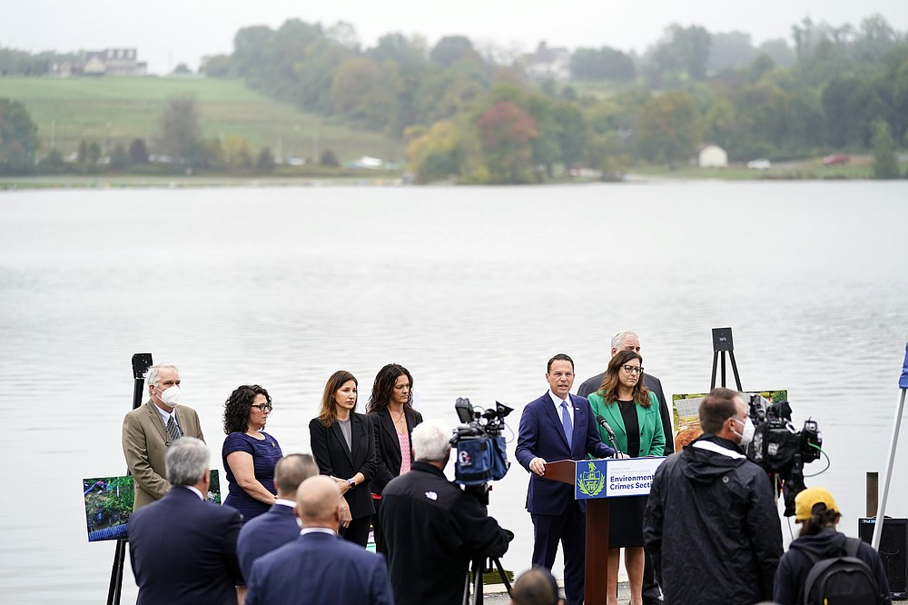 Pennsylvania Attorney General Josh Shapiro, at podium, speaks during a news conference at Marsh Creek State Park in Downingtown, Pa., Tuesday, Oct. 5, 2021. Shapiro filed criminal charges Tuesday against the developer of a problem-plagued pipeline that takes natural gas liquids from the Marcellus Shale gas field to an export terminal near Philadelphia. (AP Photo/Matt Rourke)