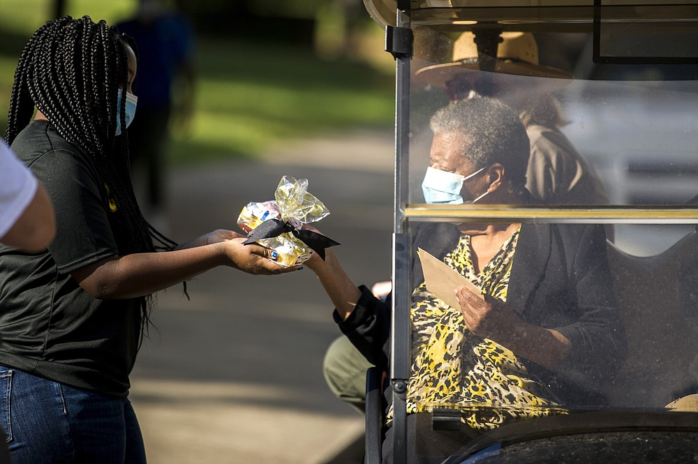 Emery Moore, 14, gives a present to Elizabeth Eckford during her 80th birthday party outside Central High School where students sang Happy Birthday and LeRon McAdoo sang a rendition of Amazing Grace Monday, Oct. 4, 2021, in Little Rock, Ark. Central High became internationally known in 1957 during the desegregation crisis. Eckford and eight other Black students were barred from entering the school by Arkansas National Guard members who had been activated, despite a court-approved desegregation plan. (Stephen Swofford/The Arkansas Democrat-Gazette via AP)