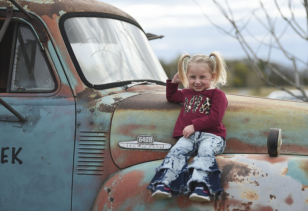 Lydia Montgomery, 5, sits on a truck as she poses for pictures, Thursday, Oct. 15, 2020 at the Benton County Fairgrounds in Bentonville. The 4th Annual Fall Y'all Craft Fair featured 40 vendors, half capacity to previous years, as well as local food trucks, photo opportunities and a pumpkin patch. The fair ends on Sunday. Check out nwaonline.com/2010013Daily/ for today's photo gallery.  (NWA Democrat-Gazette/Charlie Kaijo)