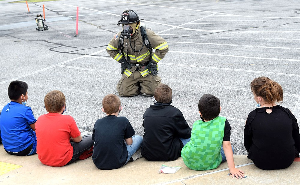 Westside Eagle Observer/MIKE ECKELS Tanner Parker, dressed in his full fire protection gear, tries talking to fourth graders at Northside Elementary through his oxygen mask during Fire Prevention Day in Decatur Oct. 1. Parker, a member of the Decatur Fire Department, was on hand Friday morning to educate kids on what to do if they become trapped in a burning building.