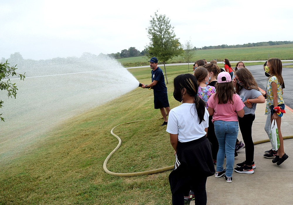 Westside Eagle Observer/MIKE ECKELS Brent Hopkins (center) demonstrates the many different settings the nozzle on the end of the fire hose is capable of performing during a structure fire. Hopkins, a member of the Decatur Fire Department, was at Northside Elementary Oct. 1 for the kickoff to the 2021 National Fire Safety Week which ran from Oct. 3 through Oct. 9.