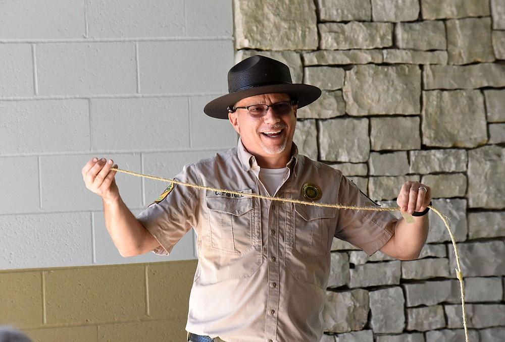 Chris Pistole, park interpreter at Hobbs State Park-Conservation Area, uses rope to show the wingspan of different birds. (NWA Democrat-Gazette/Flip Putthoff)