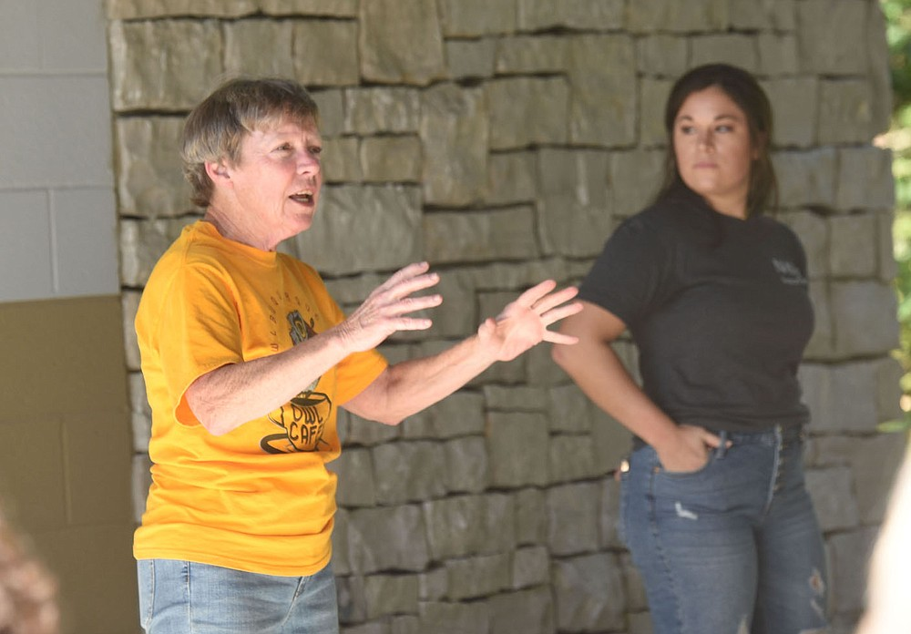 Lynn Sciumbato, a longtime federally licensed wildlife rehabilitator, talks about treating the bald eagle she released at Hobbs State Park-Conservation Area. Madison Kennedy (right) with Northsong Wild Bird Rehabilitation, hears her remarks. (NWA Democrat-Gazette/Flip Putthoff)