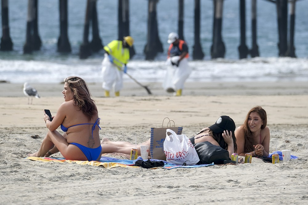 Beach goers are seen as workers in protective suits clean the contaminated beach after an oil spill, Wednesday, Oct. 6, 2021 in Newport Beach, Calif. A major oil spill off the coast of Southern California fouled popular beaches and killed wildlife while crews scrambled Sunday, to contain the crude before it spread further into protected wetlands. (AP Photo/Ringo H.W. Chiu)