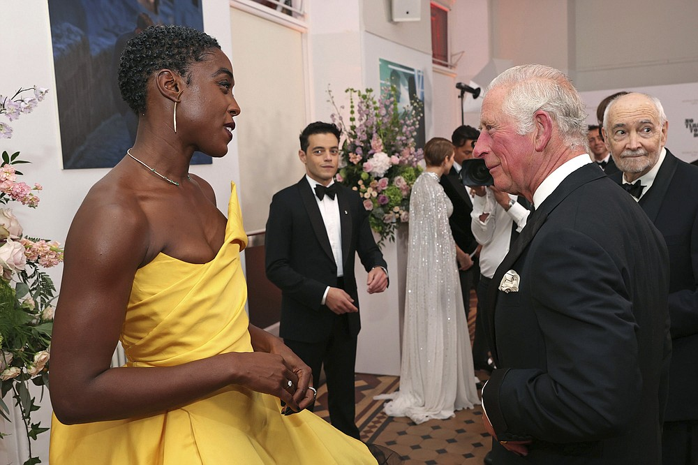 Britain's Prince Charles, right, speaks with British actress Lashana Lynch upon arrival for the World premiere of the new film from the James Bond franchise 'No Time To Die', in London, Tuesday, Sept. 28, 2021. (Chris Jackson/Pool Photo via AP)