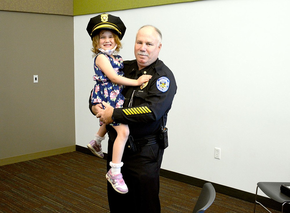 Marc Hayot/Herald-Leader Retired Deputy Chief Major Geoff Lewis (right), poses with his granddaughter Briar Florez at Lewis' retirement party on Friday at the library. Lewis served 39 years in law enforcement and 14.5 years with the Siloam Springs Police Department.