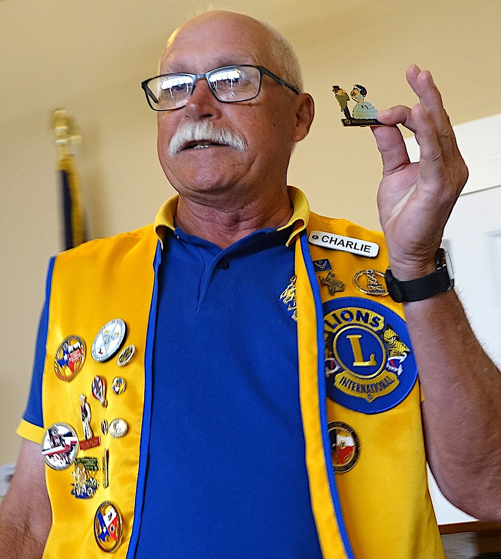 Charlie Horn, president of the Linden Lions, holds up a Lions Club pin from Louisiana he is auctioning to local members. Such pins will be worn on their jackets. Horn goes to various district meetings and buys pins from all over the world to bring back and sell to his members. It's a way to raise money for the Lions Clubs' good causes.