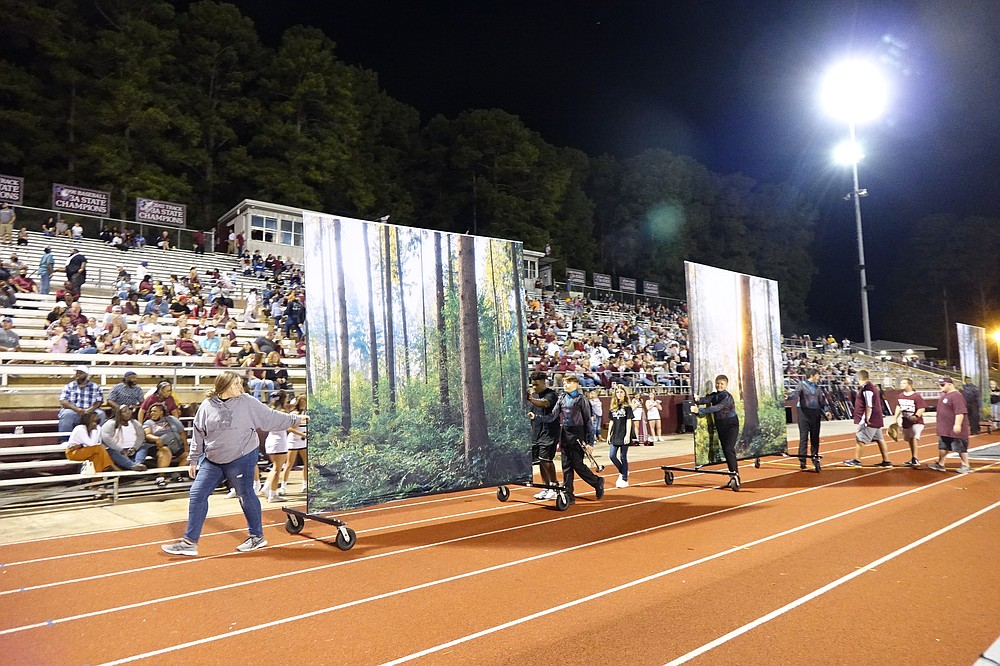 Don't look now but a forest is rolling by. Members of the Atlanta High School marching band are wheeling out backdrops for their halftime show at Rabbit Stadium. The show features birds such a raven and the phoenix, the immortal bird of Greek mythology, and so needs tree limbs to live in.