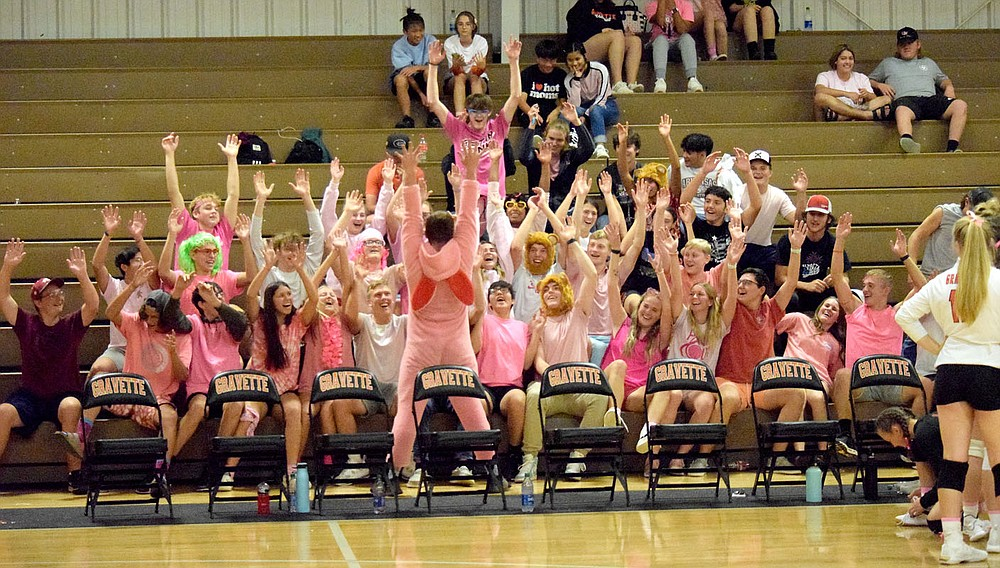 Westside Eagle Observer/MIKE ECKELS  The Gravette student secton, lead by, a pink bunny (center,) raises its hand straight up  in roller coaster fashion during the Gravette-Gentry varsity volleyball match at the Competition Gym in Gravette Thursday night. In the final home game of the volleyball season, it was pink night and almost the entire student section wore some form of the color.