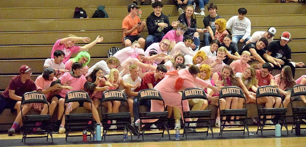 Westside Eagle Observer/MIKE ECKELS  As the pink bunny (center) points to his right, the Gravette pink student section bends over and point to their left during the break between sets of the Gravette-Gentry varsity volleyball contest in Gravette Thursday night.