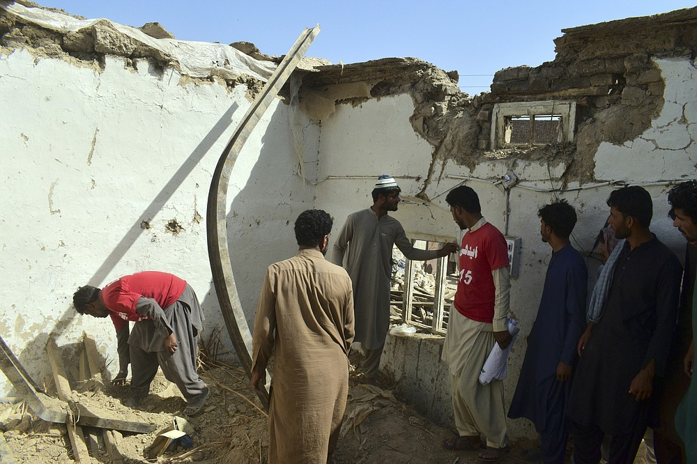 Members of a family and volunteers take belongings from a damaged house following an earthquake in Harnai, about 100 kilometers (60 miles) east of Quetta, Pakistan, Thursday, Oct. 7, 2021. The powerful earthquake collapsed at least one coal mine and dozens of mud houses in southwest Pakistan early Thursday. (AP Photo/Arshad Butt)