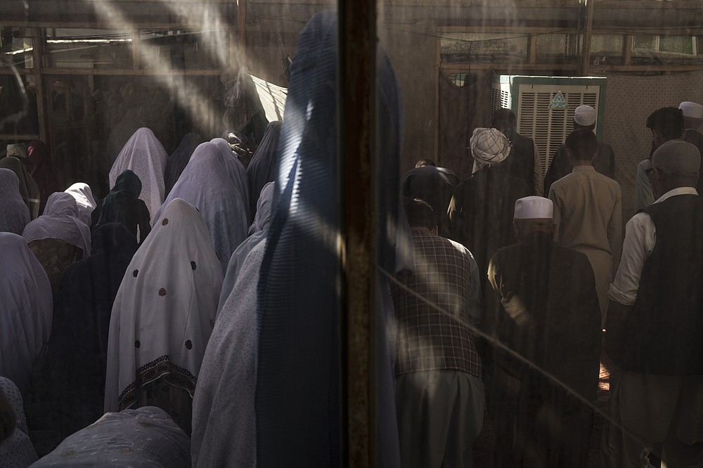 Afghan women, left, and men pray separated by a wall in a Shiite mosque during Friday prayers in Kabul, Afghanistan, Friday, Oct. 8, 2021. (AP Photo/Felipe Dana)