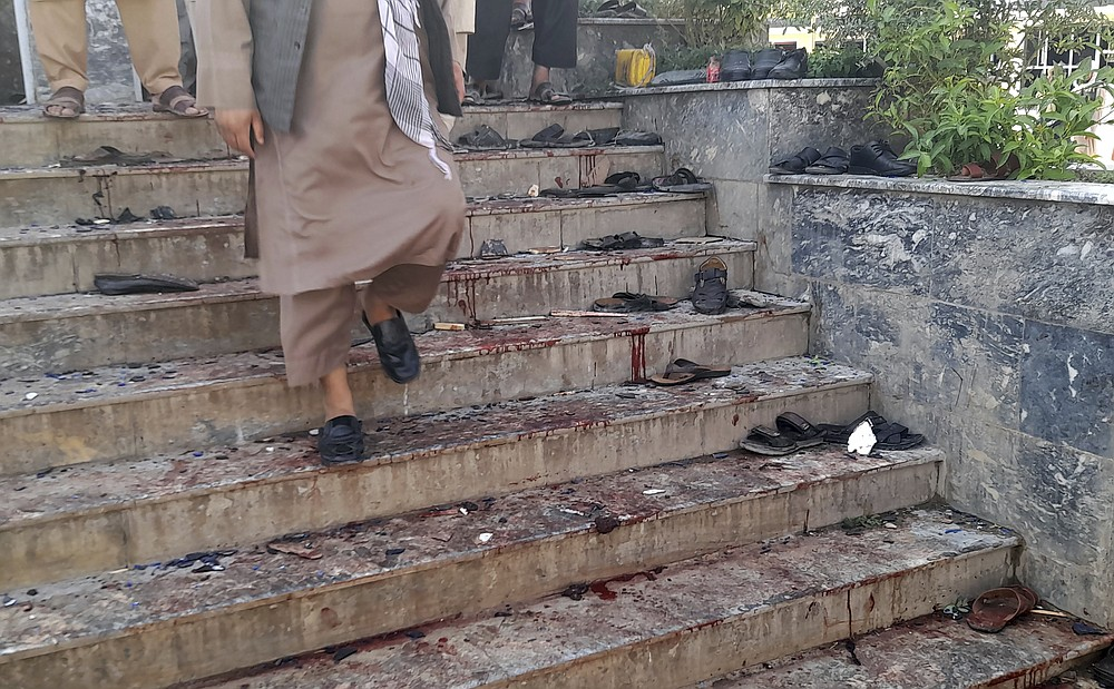 A man walks down blood-stained steps of a mosque following a bombing in Kunduz province, northern Afghanistan, Friday, Oct. 8, 2021. A powerful explosion in a mosque frequented by a Muslim religious minority in northern Afghanistan on Friday has left several casualties, witnesses and the Taliban's spokesman said. (AP Photo/Abdullah Sahil)