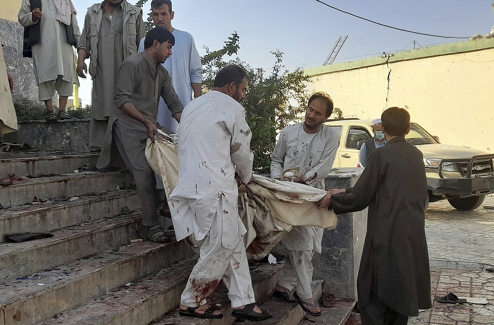 People carry the body of a victim from a mosque following a bombing in Kunduz province, northern Afghanistan, Friday, Oct. 8, 2021. A powerful explosion in a mosque frequented by a Muslim religious minority in northern Afghanistan on Friday has left several casualties, witnesses and the Taliban's spokesman said. (AP Photo/Abdullah Sahil)