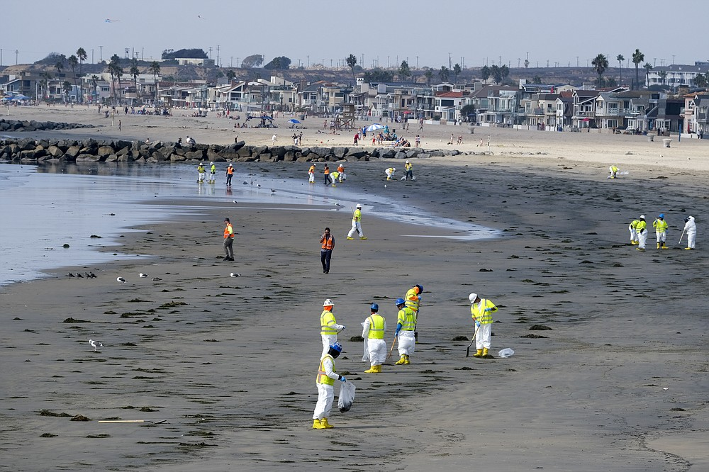Workers in protective suits clean the contaminated beach after an oil spill, Wednesday, Oct. 6, 2021 in Newport Beach, Calif. A major oil spill off the coast of Southern California fouled popular beaches and killed wildlife while crews scrambled Sunday, to contain the crude before it spread further into protected wetlands. (AP Photo/Ringo H.W. Chiu)