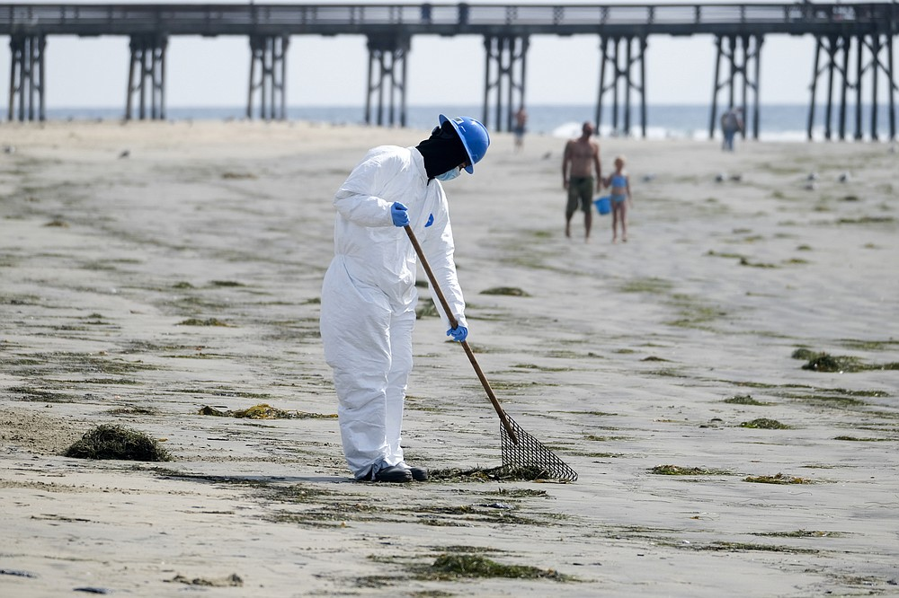 A worker in a protective suit cleans the contaminated beach after an oil spill in Newport Beach, Calif., on Wednesday, Oct. 6, 2021. A major oil spill off the coast of Southern California fouled popular beaches and killed wildlife while crews scrambled Sunday, to contain the crude before it spread further into protected wetlands. (AP Photo/Ringo H.W. Chiu)
