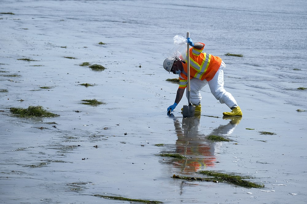 A worker in protective suit cleans the contaminated beach after an oil spill in Newport Beach, Calif., on Wednesday, Oct. 6, 2021. Some of the crude oil that spilled from a pipeline into the waters off Southern California has been breaking up naturally in ocean currents, a Coast Guard official said Wednesday as authorities sought to determine the scope of the damage.  (AP Photo/Ringo H.W. Chiu)