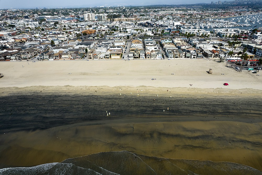 In this aerial image taken with a drone, workers in protective suits clean the contaminated beach after an oil spill in Newport Beach, Calif., on Wednesday, Oct. 6, 2021. Some of the crude oil that spilled from a pipeline into the waters off Southern California has been breaking up naturally in ocean currents, a Coast Guard official said Wednesday as authorities sought to determine the scope of the damage.  (AP Photo/Ringo H.W. Chiu)