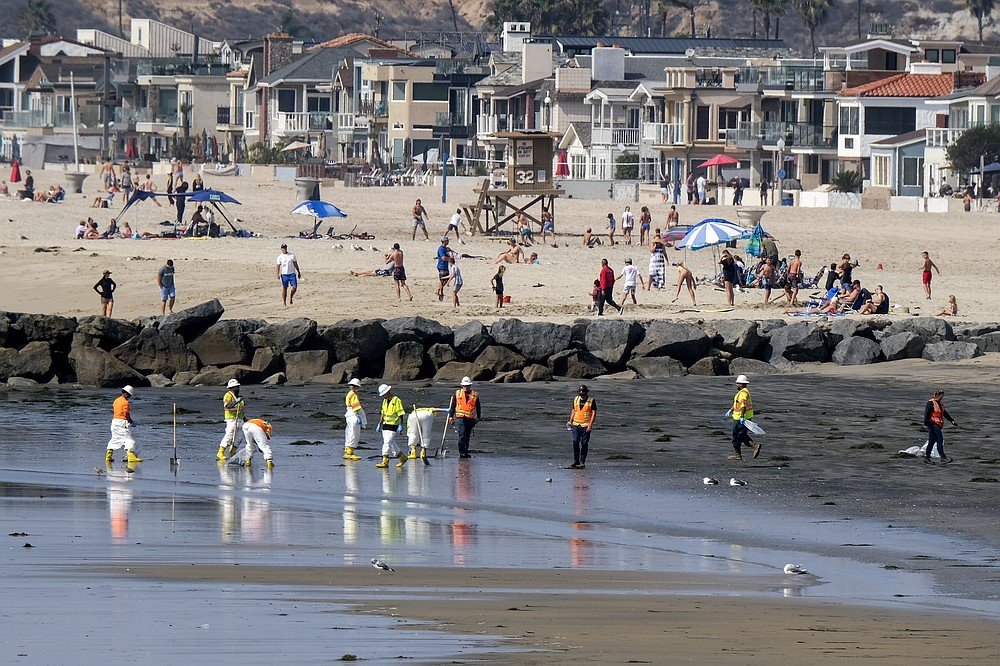 People play on the sand in the background as workers in protective suits clean the contaminated beach after an oil spill in Newport Beach, Calif., on Wednesday, Oct. 6, 2021. A major oil spill off the coast of Southern California fouled popular beaches and killed wildlife while crews scrambled Sunday, to contain the crude before it spread further into protected wetlands. (AP Photo/Ringo H.W. Chiu)