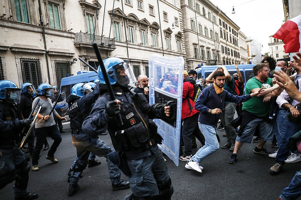 Police clashes with demonstrators during a protest, in Rome, Saturday, Oct. 9, 2021. Thousands of demonstrators protested Saturday in Rome against the COVID-19 health pass that Italian workers, both the public and private sectors, must display to access their workplaces from Oct. 15 under a government decree. (Cecilia Fabiano/LaPresse via AP)