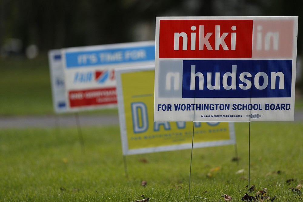 Campaign yard signs line a yard Thursday, Oct. 7, 2021, in Worthington, Ohio. Across Ohio and the nation, parental protests over social issues like mask mandates, gender-neutral bathrooms, teachings on racial history, sexuality and mental and emotional health are being leveraged into school board takeover campaigns. (AP Photo/Jay LaPrete)