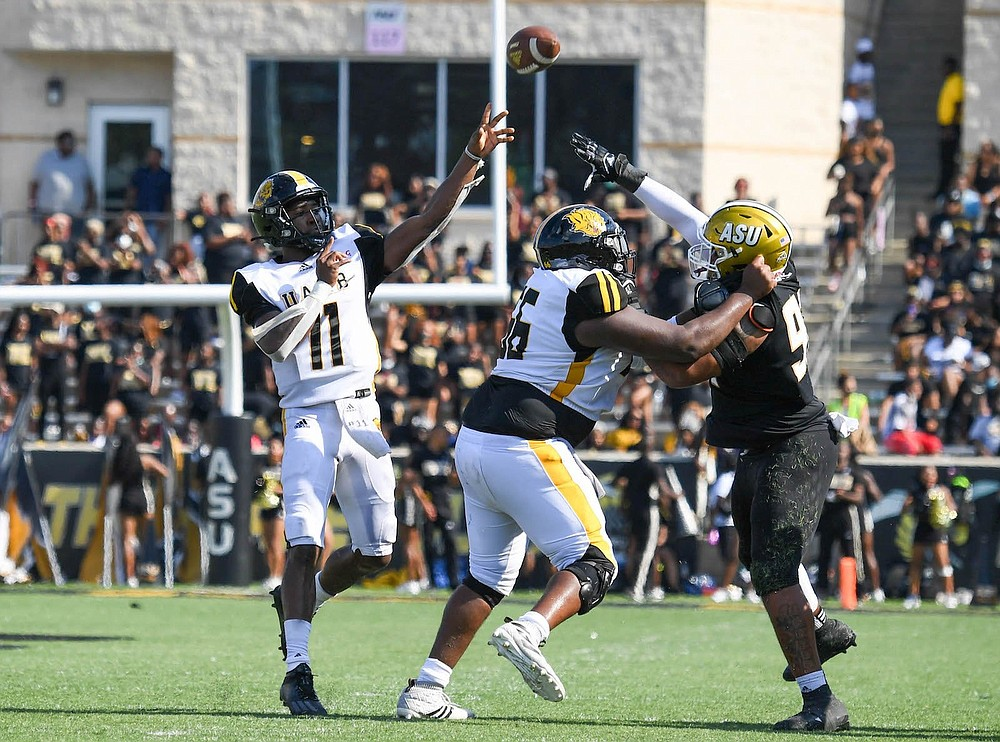 UAPB quarterback Skyler Perry lofts a pass as offensive lineman Eric Jones III blocks an Alabama State pass rusher on Saturday in Montgomery, Ala. (Special to The Commercial/Brian Tannehill)