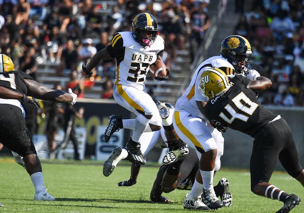 UAPB running back Kayvon Britten hurdles over a would-be tackler as a teammate blocks Alabama State linebacker Demarkus Cunningham on Saturday in Montgomery, Ala. (Special to The Commercial/Brian Tannehill)