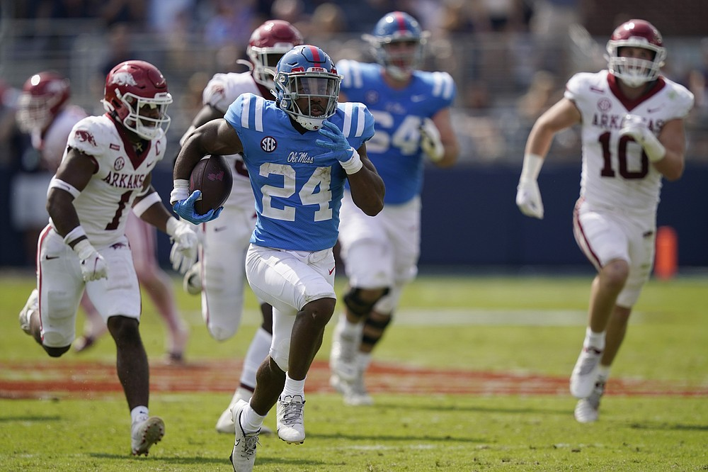 Mississippi running back Snoop Conner (24) runs past a host of Arkansas defenders on his way to a 51-yard touchdown run during the second half of an NCAA college football game, Saturday, Oct. 9, 2021, in Oxford, Miss. Mississippi won 52-51.(AP Photo/Rogelio V. Solis)