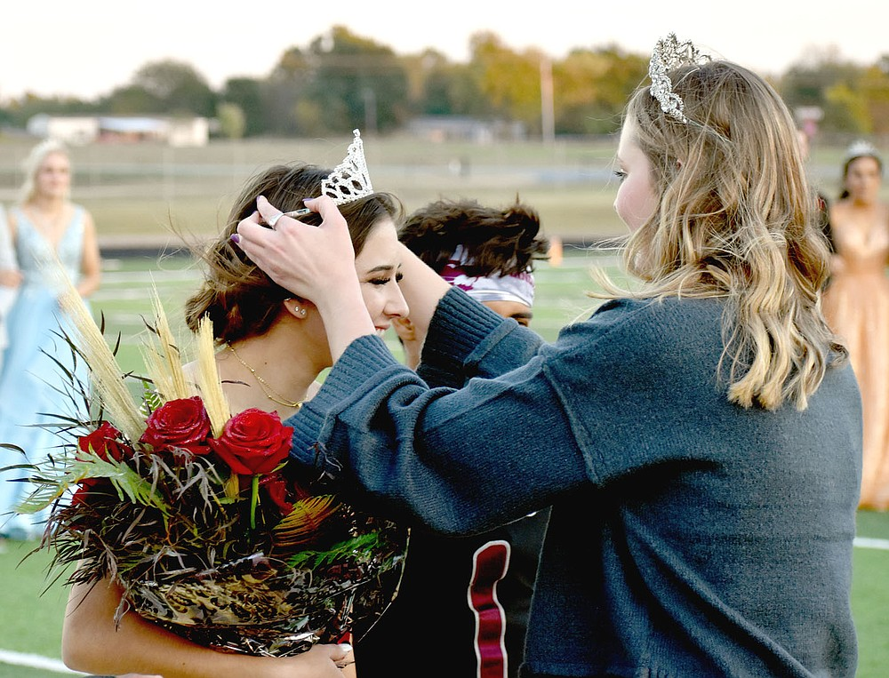 MARK HUMPHREY  ENTERPRISE-LEADER/Lincoln senior Emily Meckley receives the 2021 Homecoming crown from 2020 Homecoming queen Keara Wallace, daughter of Shane Wallace and Jennifer Price.