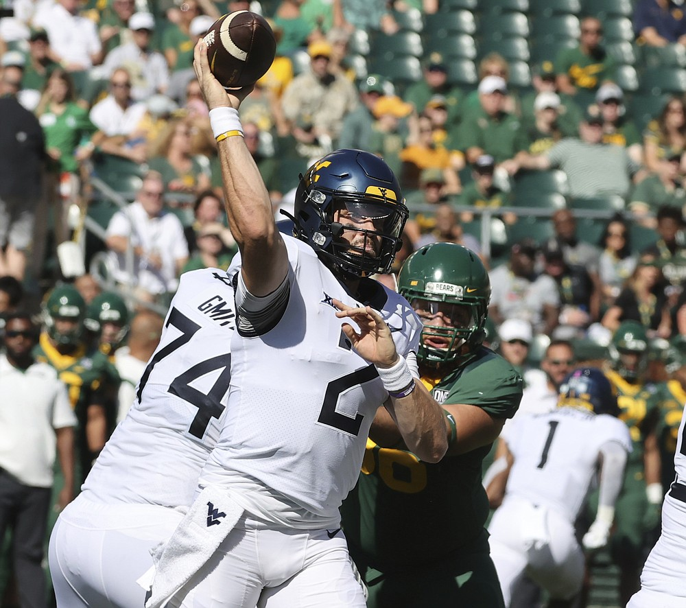 West Virginia quarterback Jarret Doege throws to the sideline while being pressured by Baylor in the first half of an NCAA college football game, Saturday, Oct. 9, 2021, in Waco, Texas. (Rod Aydelotte/Waco Tribune-Herald via AP)