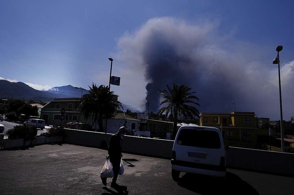 A man carries groceries from a supermarket as a volcano continues to erupt in El Paso on the canary island of La Palma, Spain, Saturday Oct. 9, 2021. A new lava flow has belched out from the La Palma volcano and it threatens to spread more destruction on the Atlantic Ocean island where molten rock streams have already engulfed over 1,000 buildings. The partial collapse of the volcanic cone overnight sent a new lava stream Saturday heading toward the western shore of the island. (AP Photo/Daniel Roca)