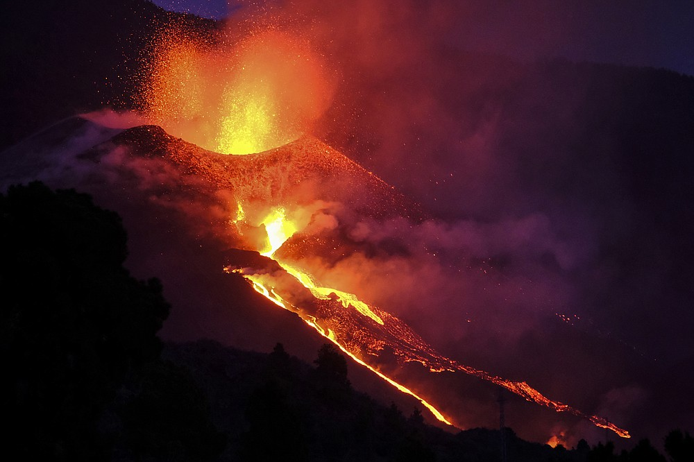 Lava flows from a volcano on the Canary island of La Palma, Spain, Saturday Oct. 2, 2021. An erupting volcano on a Spanish island off northwest Africa has blown open another fissure on its hillside. The new fissure is the third to crack open since the Cumbre Vieja crater erupted on La Palma island Sept. 19. (AP Photo/Daniel Roca)