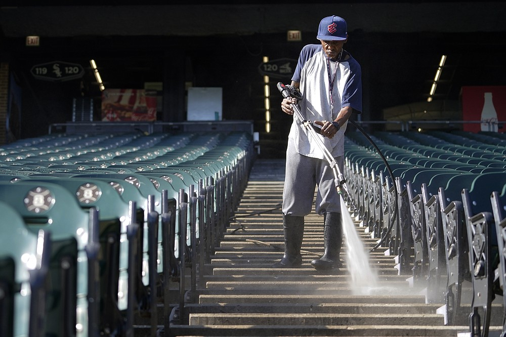 A stadium worker cleans the seating area during baseball practice for the American League Division Series, Saturday, Oct. 9, 2021, in Chicago. The Chicago White Sox host the Astros in Game 3 on Sunday. (AP Photo/Nam Y. Huh)