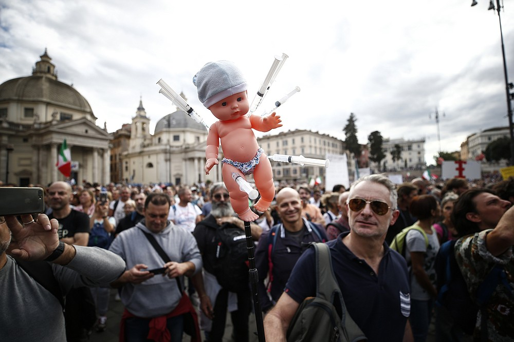 A doll with syringes is shown by a demonstrator during a protest, in Rome, Saturday, Oct. 9, 2021. Thousands of demonstrators protested Saturday in Rome against the COVID-19 health pass that Italian workers, both the public and private sectors, must display to access their workplaces from Oct. 15 under a government decree. (Cecilia Fabiano/LaPresse via AP)
