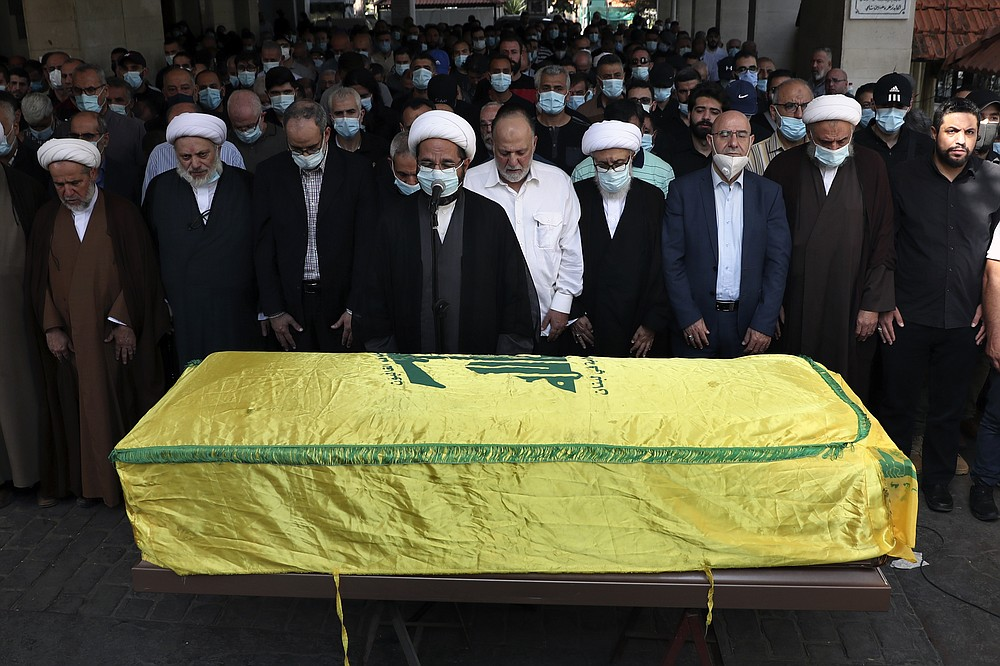 Relatives, friends and clergymen pray in front of the coffin of Ali Atwa, a senior Hezbollah operative, during his funeral procession in the southern Beirut suburb of Dahiyeh, Lebanon, Saturday, Oct. 9, 2021. Atwa was placed on the FBI's most wanted list in 2001, with two other alleged participants in the 1985 hijacking of TWA Flight 847, one of the worst hijackings in aviation history and that lasted for 16 days. (AP Photo/Bilal Hussein)