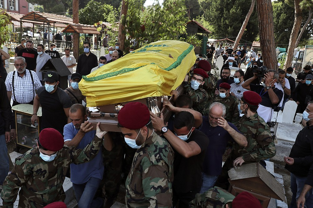 Hezbollah fighters carry the coffin of Ali Atwa, a senior Hezbollah operative, during his funeral procession in the southern Beirut suburb of Dahiyeh, Lebanon, Saturday, Oct. 9, 2021. Atwa was placed on the FBI's most wanted list in 2001, with two other alleged participants in the 1985 hijacking of TWA Flight 847, one of the worst hijackings in aviation history and that lasted for 16 days. (AP Photo/Bilal Hussein)