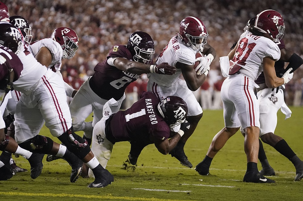 Alabama running back Brian Robinson Jr. (4) is tackled short of the goal line by Texas A&M linebacker Aaron Hansford (1) and defensive lineman DeMarvin Leal (8) during the first half of an NCAA college football game Saturday, Oct. 9, 2021, in College Station, Texas. (AP Photo/Sam Craft)