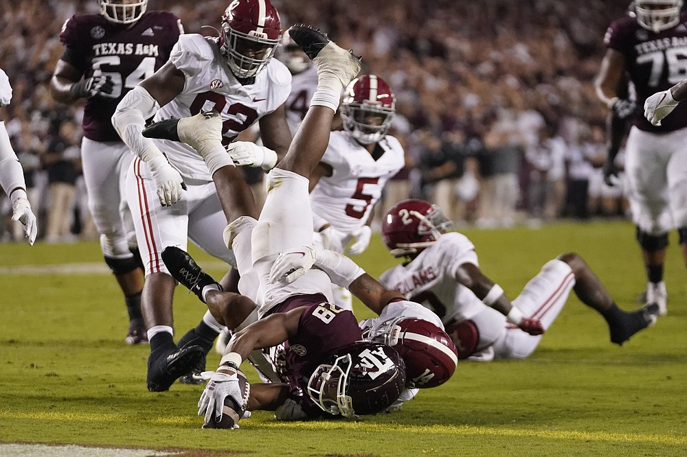 Texas A&M running back Isaiah Spiller (28) dives over the goal line for a touchdown as Alabama defensive back Brian Branch (14) defends during the first half of an NCAA college football game Saturday, Oct. 9, 2021, in College Station, Texas. (AP Photo/Sam Craft)