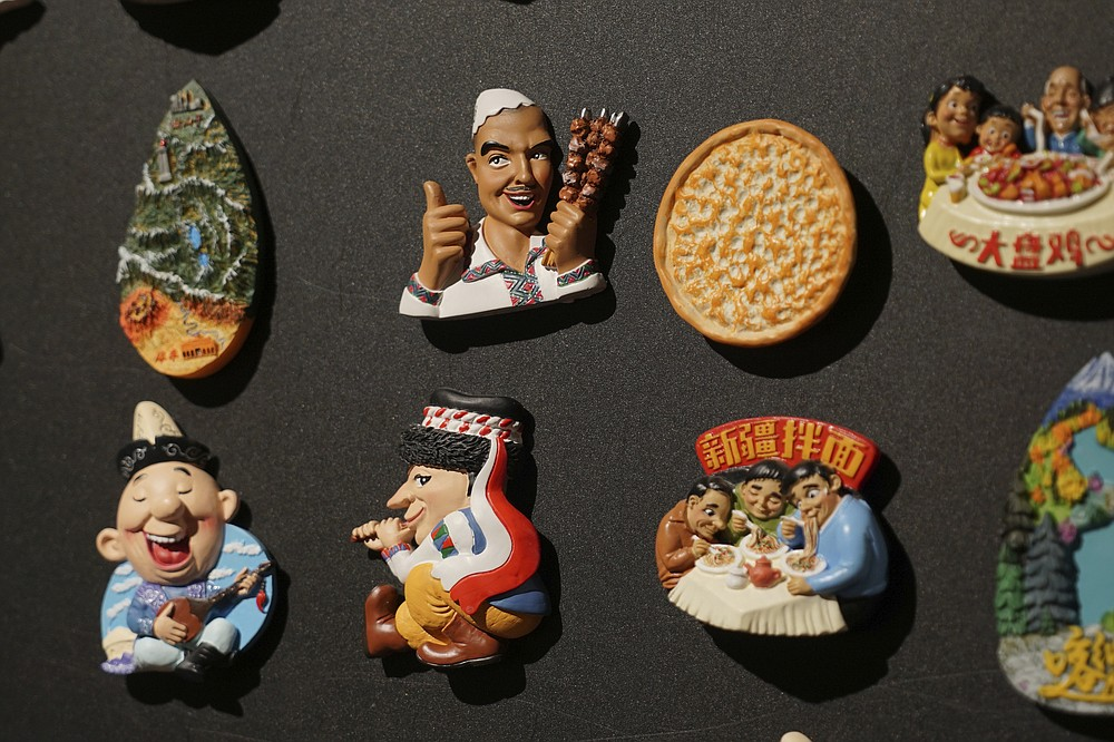 Uyghur-themed fridge magnets are displayed at a naan museum in Urumqi, the capital of China's far west Xinjiang region, on April 21, 2021. Four years after Beijing's brutal crackdown on largely Muslim minorities native to Xinjiang, Chinese authorities are dialing back the region's high-tech police state and stepping up tourism. But even as a sense of normality returns, fear remains, hidden but pervasive. (AP Photo/Dake Kang)