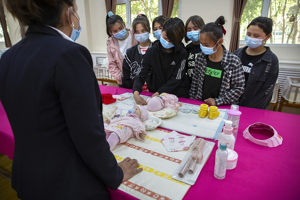 An instructor teaches Uyghurs how to change a diaper during a class at the Peyzawat Training School in Peyzawat County in China's far west Xinjiang region, as seen during a state-organized tour for foreign media on April 19, 2021. Four years after Beijing's brutal crackdown on largely Muslim minorities native to Xinjiang, Chinese authorities are dialing back the region's high-tech police state and stepping up tourism. But even as a sense of normality returns, fear remains, hidden but pervasive. (AP Photo/Mark Schiefelbein)