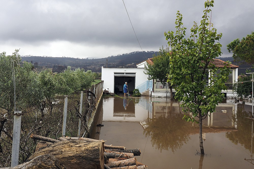 A woman stands at the yard of her house at Achladi village following a flood on the northern part of Evia island, Greece, Sunday, Oct. 10, 2021. The wildfires that destroyed a third of the island's forests in early August have loosened the topsoil and several communities are at risk from flooding. (AP Photo/Thodoris Nikolaou)