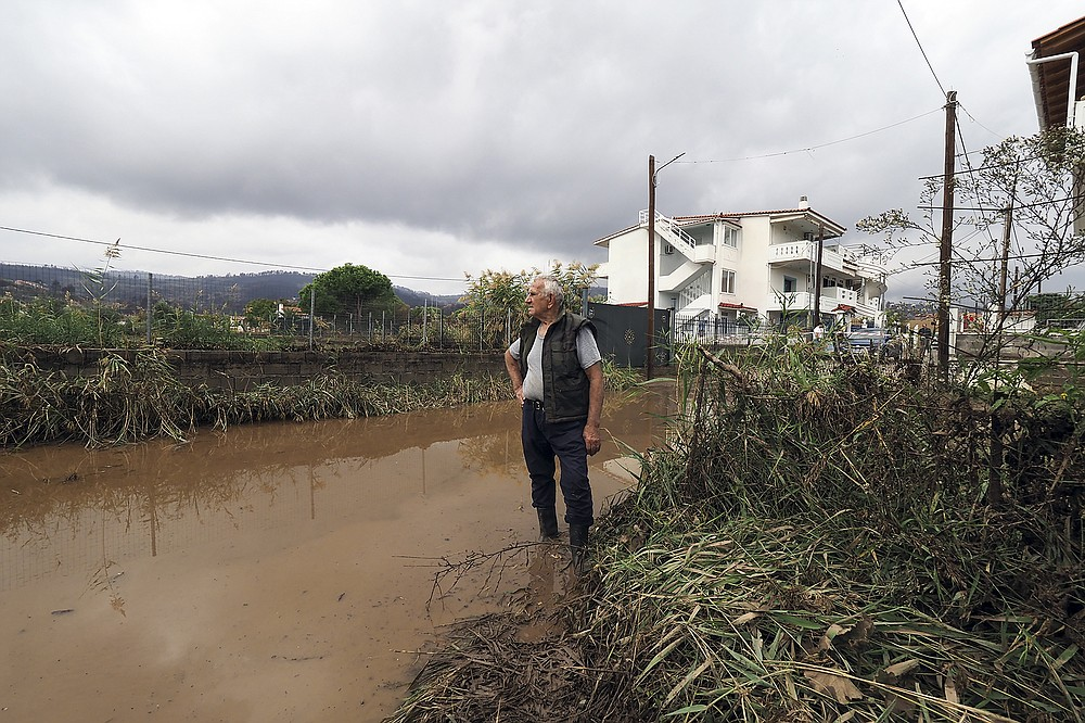 A man stands on a flooded road at Agia Anna village, following a flood on the northern part of Evia island, Greece, Sunday, Oct. 10, 2021. The wildfires that destroyed a third of the island's forests in early August have loosened the topsoil and several communities are at risk from flooding. (AP Photo/Thodoris Nikolaou)