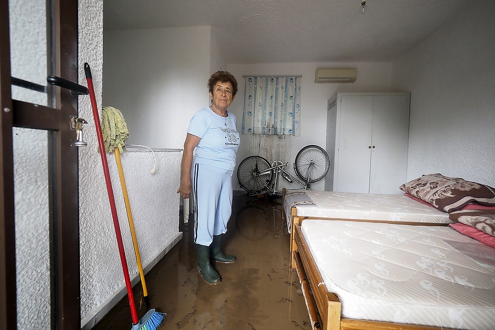 A woman stands inside her house at Achladi village following a flood on the northern part of Evia island, Greece, Sunday, Oct. 10, 2021. The wildfires that destroyed a third of the island's forests in early August have loosened the topsoil and several communities are at risk from flooding. (AP Photo/Thodoris Nikolaou)