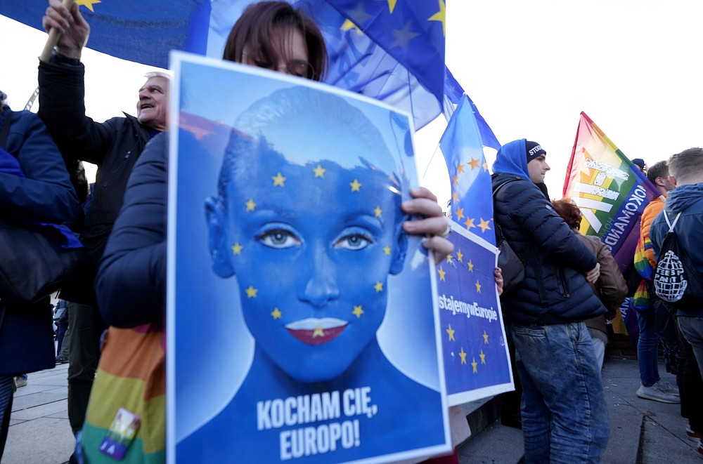 A woman holds a sign in support of Poland's EU membership which reads 'I love you Europe' during a demonstration, in Warsaw, Poland, Sunday, October 10, 2021. Poland's constitutional court ruled Thursday that Polish laws have supremacy over those of the European Union in areas where they clash, a decision likely to embolden the country's right-wing government and worsen its already troubled relationship with the EU. (AP Photo/Czarek Sokolowski)