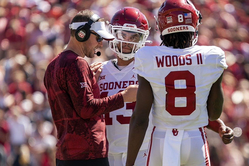Oklahoma head coach Lincoln Riley talks with quarterback Caleb Williams (13), who replaced Spencer Rattler during the game, and wide receiver Michael Woods II (8) during the second half of an NCAA college football game against Texas at the Cotton Bowl, Saturday, Oct. 9, 2021, in Dallas. Oklahoma won 54-48. (AP Photo/Jeffrey McWhorter)