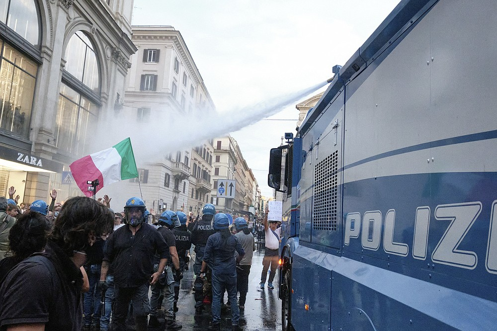 Demonstrators are sprayed by police water cannon as clashes occur during a protest, in Rome, Saturday, Oct. 9, 2021. Thousands of demonstrators protested Saturday in Rome against the COVID-19 health pass that Italian workers, both the public and private sectors, must display to access their workplaces from Oct. 15 under a government decree. (Mauro Scrobogna/LaPresse via AP)
