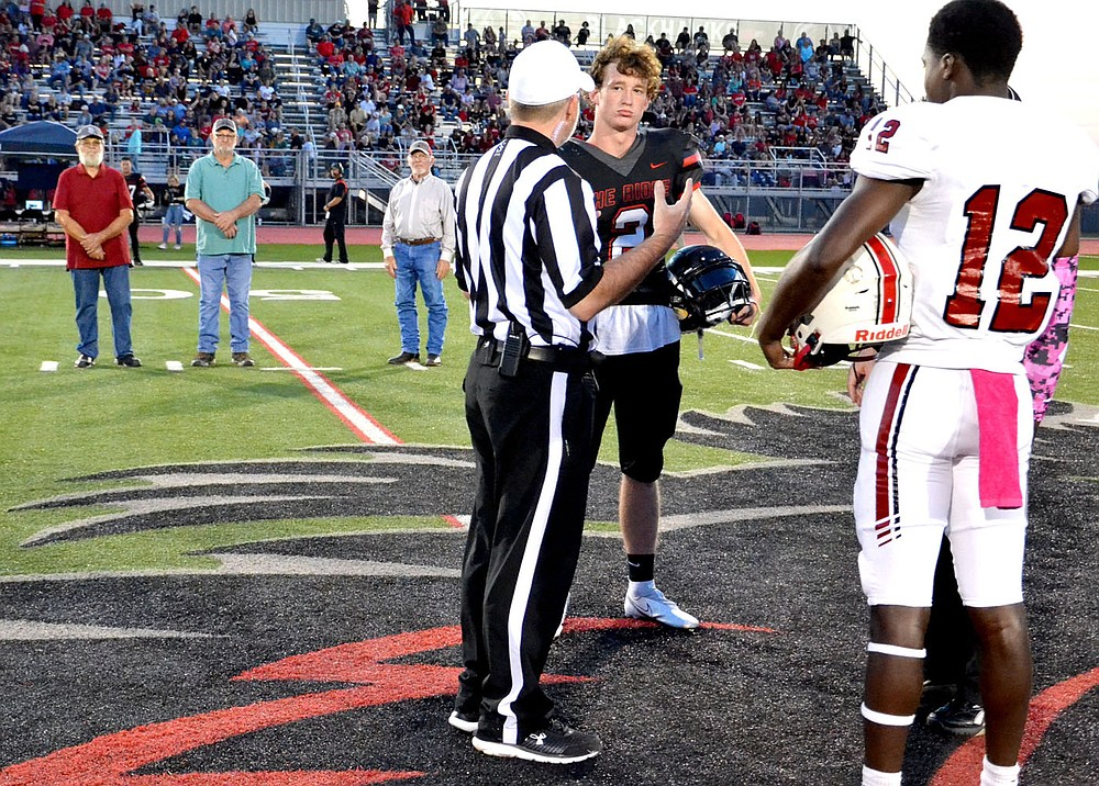 TIMES photograph by Annette Beard Blackhawk football captain Joe Adams, No. 2, met in center field for the coin toss as honorary captains J.C. Beaver, Steve Patton and Doug McKinney looked on. The honorary captains were members of the1963 Blackhawk football team as the first Pea Ridge football team in school history.
