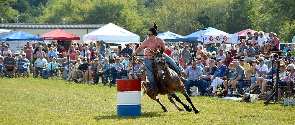 Colleen Born of Afton, Okla., and Comet round a barrel during the flag race Saturday.